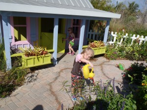 Girls watering plants outside playhouse